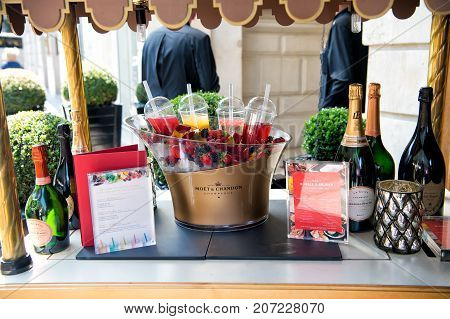 Paris France - June 01 2017: menu champagne bottles fresh berries on ice and coctails on table. Bar counter outdoors on building background. Buffet brunch luxury hotel concept.
