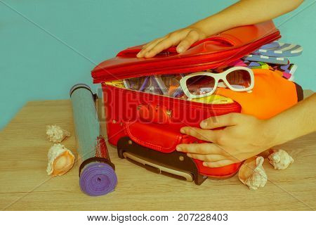 Young girl packing suitcase at home. Open suitcase packed for travelling close up - Retro color