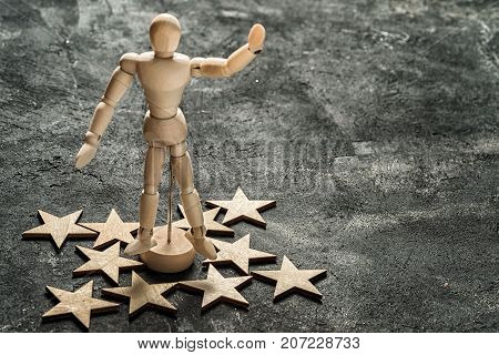 wooden mannequin stands in the center of a figure of stars on a black textured cement background showing a hand greeting gesture with copy space for your text