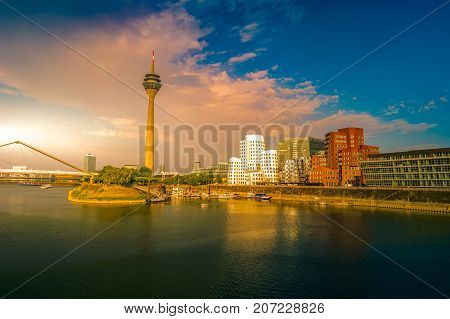 Looking at Media Harbor at Rhine-River in Dusseldorf in Germany. Media Harbor with Rhine-Tower and famous buildings in dramatic sunset light with their reflection in the water. Beautiful and colorful cityscape of the german city