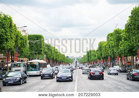 Paris France - June 02 2017: avenue Elysian Fields with street traffic and green trees on cloudy sky background. Landmark and sightseeing. Summer vacation and travel concept triumphal arch road