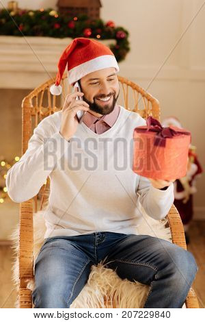 Sincere gratitude. Joyful handsome man sitting in a rocking chair and talking on the phone while thanking his interlocutor for a gift in his hands