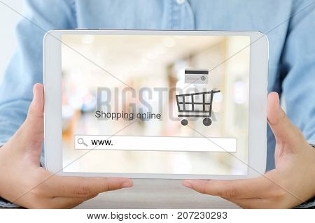 Hand holding tablet with www. on search bar over blur store background on screen on line shopping business and technology E-commerce digital marketing concept
