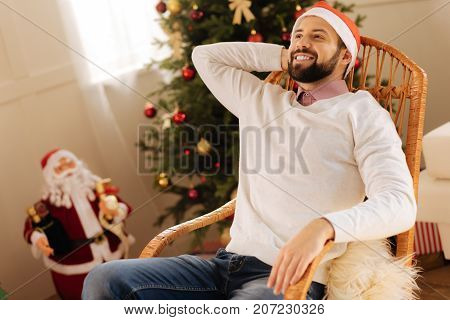Laid-back weekend. Happy young man relaxing with a beaming smile while sitting in a rocking chair in the room with Christmas decorations