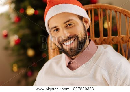 Happy holidays. Charming bearded young man in Santa hat sitting in a rocking chair and smiling at the camera
