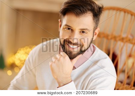 Pleasant ambience. The portrait of a handsome joyful young man sitting in a cozy room and smiling at the camera broadly while resting his chin on his hand