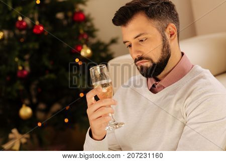 Forever alone. Disappointed young man sitting on the floor near a Christmas tree and looking sadly on the glass of champagne, being all alone on Christmas Eve