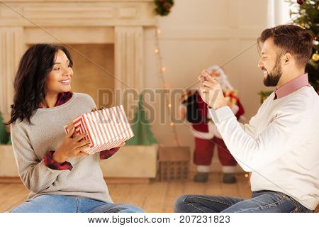For family archive. Happy young man taking a photo of his beloved wife sitting on the floor in the room with Christmas decorations and holding a gift box