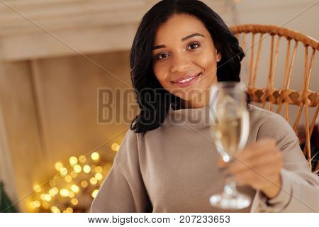 Cheers to us. The focus being on a beautiful dark-haired woman sitting in a rocking chair and handing a glass of champagne to the camera while smiling