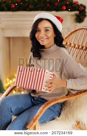Memorable present. Pretty dark-haired woman sitting in a rocking chair and posing with a Christmas gift in her hands while smiling happily in the camera