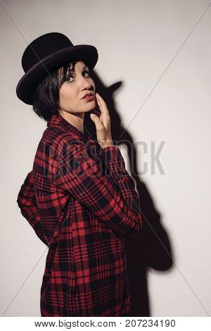 Attractive girl in red checkered shirt and hat bowler stands near white wall raising her hand to face