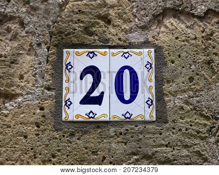 House number twenty (20): ceramic tiles with blue figures on old stone wall. Traditional Italian home sign board painted on ceramic tile