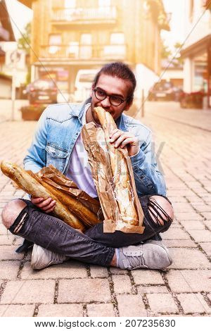 Young man with glasses sits in the morning with sunshine in the pedestrian zone and eats a baguette.