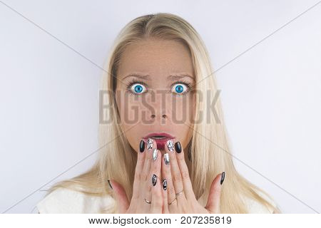 Surprised blond girl with blue eyes screams and closes mouth with her hands from surprise. Presenting your product. Isolated on white background. Expressive facial expressions. Surprised happy young woman