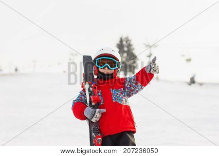 Little Cute Boy With Skis And A Ski Outfit. Little Skier In The Ski Resort. Winter Holidays