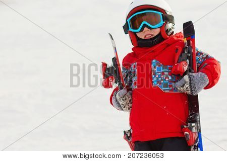 Little Cute Boy With Skis And A Ski Outfit. Little Skier In The Ski Resort. Winter Holidays.