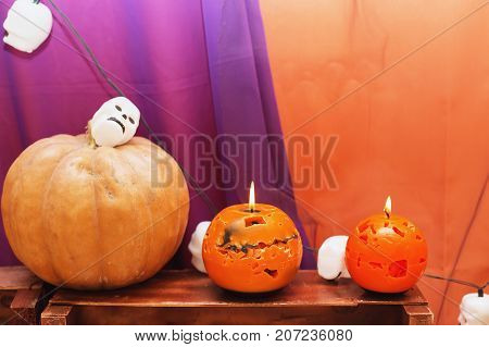 orange candles Halloween pumpkin and garland in the shape of skulls on textured surface in front of violet backdrop. Souvenir gift candle in the shape of Carved pumpkin. A burning candle. Candle lit. Halloween decorations