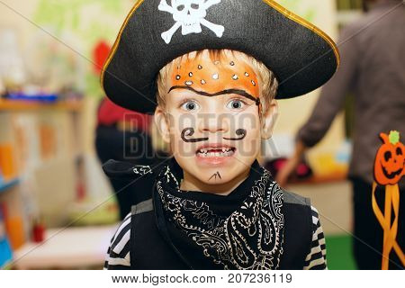 Halloween Party. A Little Boy In A Pirate Costume And A Makeup On His Face Is Having A Good Time At