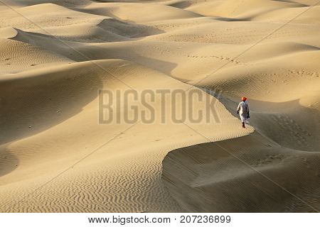 Indian bedouin is going all over the peak of the sand dune on the Thar desert Rajasthan India