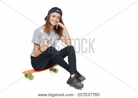 Teen girl in full length sitting on skate board holding a bottle with water smiling at camera, isolated on white background
