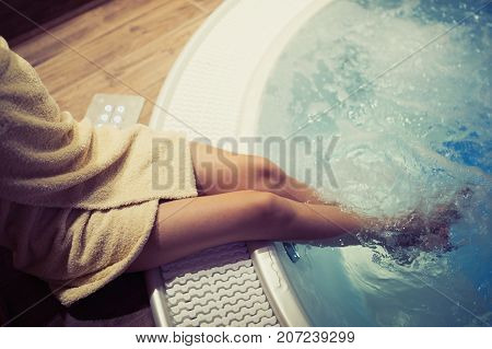 Woman with beautiful legs entering hot tub in spa resost