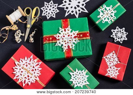 Decoration of gift boxes for Christmas with your own hands. DIY hobby. Boxes are wrapped in red and green paper tied with ribbons with handmade snowflakes. Original gift decoration
