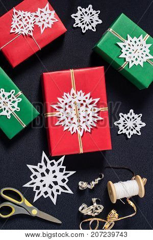 Decoration of gift boxes for Christmas with your own hands. DIY hobby. Boxes are wrapped in red and green paper tied with ribbons with handmade snowflakes. Original gift decoration. Vertical