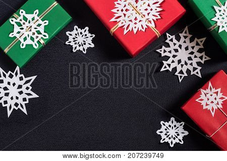 Christmas background with handmade gift boxes and snowflakes. Boxes are wrapped in red and green paper tied with ribbons with snowflakes. Original gift decoration DIY hobby