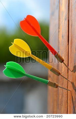 Three darts at wooden board.