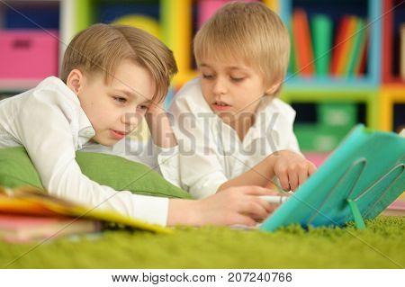two bored boys doing homework while lying on green carpet