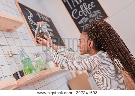 Barista Holding Jar With Coffee Beans