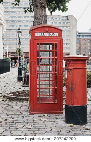 LONDON, UK - SEPTEMBER 30, 2017: An iconic red telephone box next to a red post box in St Katharine Docks, London. Red phone boxes can be found in current or former British colonies around the world