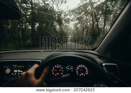 Inside view of car dashboard with hand in the steering wheel while driving across australian road.