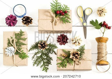 Homemade gift box decoration for Christmas. DIY hobby. Boxes are wrapped in kraft paper tied with twine with twigs of thuja cones and berries. Original gift decoration