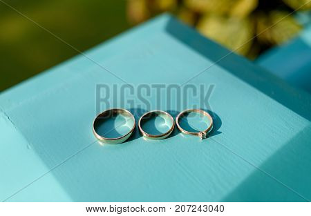 Three wedding rings on turquoise wooden background selective focus. Engagement ring with diamond bridal ring and groom ring free space. Accessories for wedding day. Proposal and wedding concept
