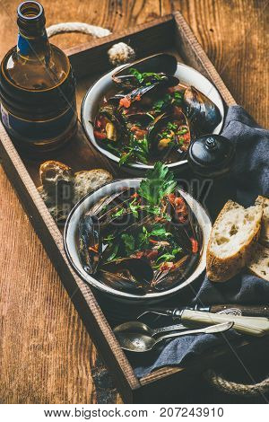 Belgian boiled mussels in tomato sauce with fresh parsley in serving metal bowls and baguette bread slices and beer in bottle in wooden tray over rustic background, selective focus