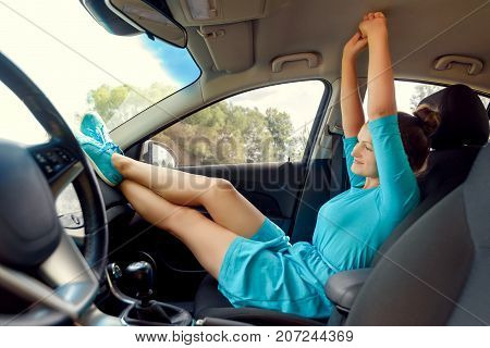 Girl In Car Sitting On Front Passenger Seat With Feet On Car Dashboard With Hands Up. Young Woman Re