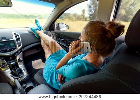 Girl in car sitting on passenger seat with feet on car dashboard and talking on mobile cell phone. Young woman relaxing with feet on dashboard. Freedom travel concept. Spending weekend in roadtrip