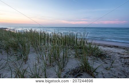 Evening Beach Backgrounds. Dune grass and sand dunes on a warm summer evening on the shores of Lake Huron in the Lower Peninsula of Michigan.