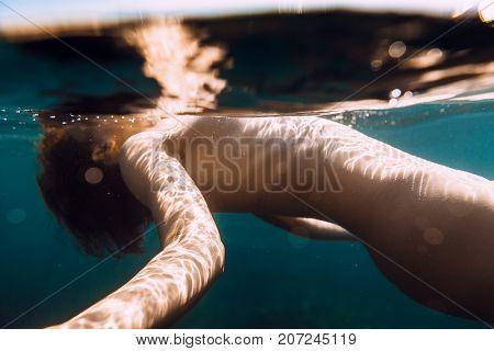 Beautiful girl is underwater. Woman floating in sea