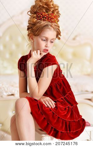 Emotional little girl in red velvet dress with retro hairstyle sitting on beige couch