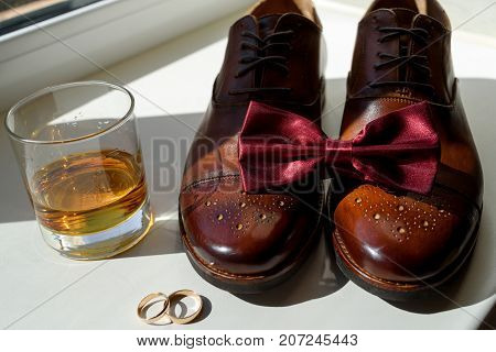 Close Up Of Burgundy Bowtie On Brown Leather Man Shoes, Wedding Rings And Glass Of Cognac. Modern Ma