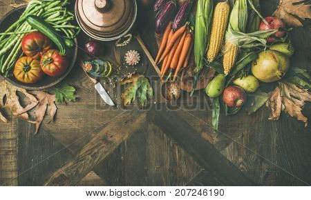 Fall healthy cooking background. Ingredients for Thanksgiving day dinner. Flat-lay of beans, corn corn, carrot, tomatoes, eggplants, fruits and fallen leaves over wooden table, top view, copy space