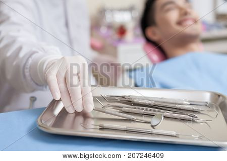 Dentist hand pick some instruments from metal tray in clinic. Dental care and healthy maintenance concept