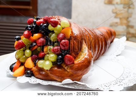 Sweet cake with berries for holidays on table close-up free space. Cornucopia horn of plenty day of rich harvest. Wedding cake
