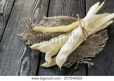 Bunch of white string beans tied with twine. Long white pods on sackcloth on dark wooden table. New harvest. Ingredient in healthy and dietary food