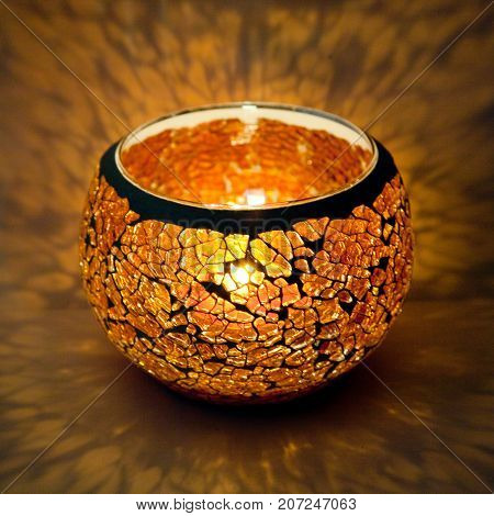 A beautiful candlestick ball of orange  glass with rays of light, with a glowing candle inside