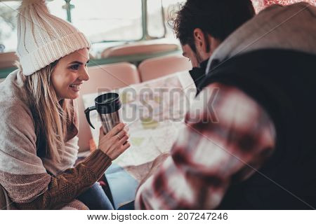 Couple of friends on roadtrip sitting at the back in their camper van. Smiling woman holding coffee and man looking at the map.