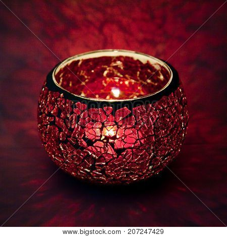 A beautiful candlestick ball of pink glass with rays of light, with a glowing candle inside