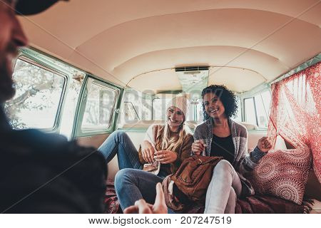 Friends on roadtrip smiling and laughing inside van. Young people travelling together in a van and having fun.